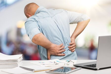 Business man with back pain sin an office . Pain relief concept