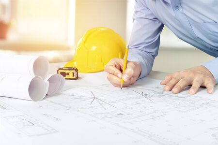 Construction concept of Engineer or architect meeting for project working with partner and engineering tools on model building and blueprint in working site.