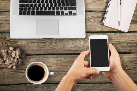 mains d'homme tenant un smartphone avec écran blanc pour la publicité. Vue de dessus des mains, clavier d'ordinateur portable, café, mobile sur fond de table en bois foncé, espace de copie Banque d'images