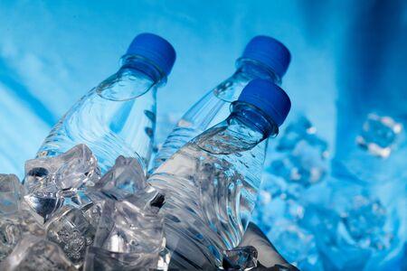 Tres botellas de agua en un cubo de hielo sobre el fondo azul.