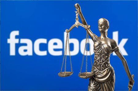 Blind folded Lady Justice statue in front of a laptop with social network Facebook logo on the screen, depicting the launch of Facebook's crypto currency Libra credit