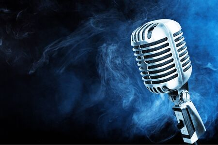 Silver microphone closeup on blue smoke background