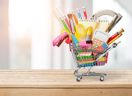 Stationery objects in mini supermarket cart on background Stock Photo