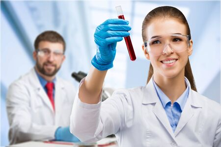 Young attractive female scientist in protective glasses and gloves dropping a red liquid substance into the test tube with a long glass pipette in the scientific chemical laboratory Foto de archivo