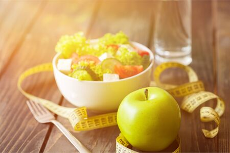 Salad in white bowl, fresh green apple and tape measure on dark wooden background. Diet and weight loss concept. Imagens