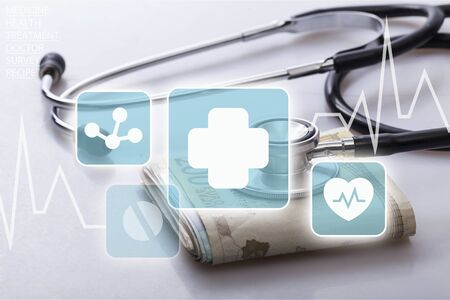 a stethoscope on a wad of euro bills, depicting the concept of the health care industry or the health care costs Stock fotó