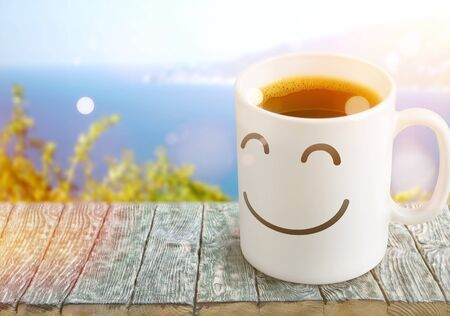 Black coffee in white cup with smiley on it on wooden  background