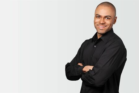 Interested african american man touching chin and smiling, white studio background, copy space          - Image