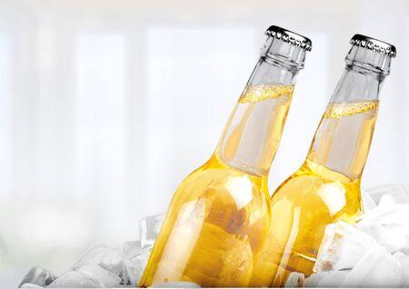 Butelki zimnego i świeżego piwa z lodem na białym tle