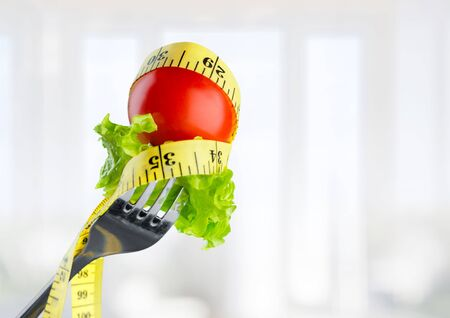 Fresh raw vegetables on fork and measuring tape on background