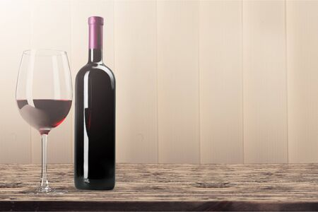 Red wine glass and bottle on wooden desk background Stockfoto