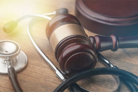 Gavel and stethoscope on wooden background, symbol photo for bungling and medical error