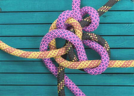 Knot on a colorful cord  on wooden background Imagens