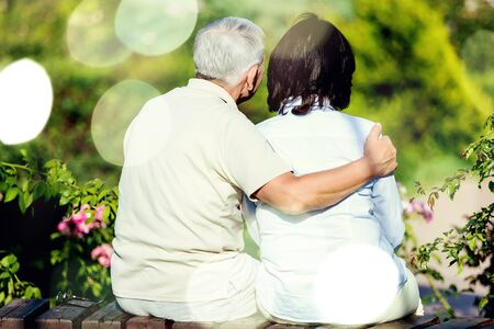 Close-up portrait of an elderly couple hugging in park