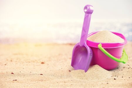 Colored toys on sandy seacoast. Travel concept
