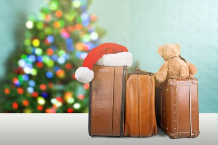 Stack of Old suitcases with teddy bear and santa hat . Travelling concept