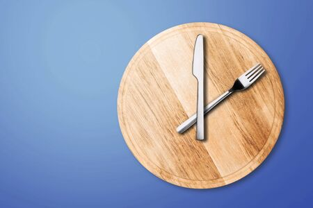 Intermittent fasting and skip breakfast concept - wooden round tray or trencher with cutlery as clock hands on lilac background. Eight hour feeding window concept or breakfast time concept. Copy space Stock fotó