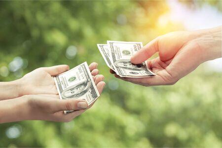 Hands holding one hundred dollars banknote over background