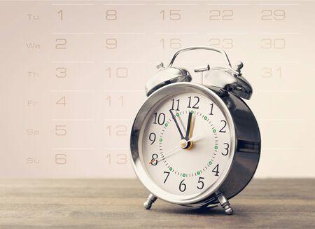 Gray retro alarm clock on wooden table background