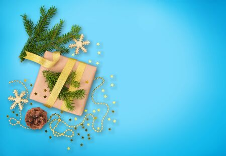 Christmas gift box with golden decorations and sparkles on blue bacground. Gift box tied with blue ribbon. Holiday banner. Stock Photo