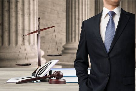 Lawyer standing near Scales of Justice on the background Stockfoto