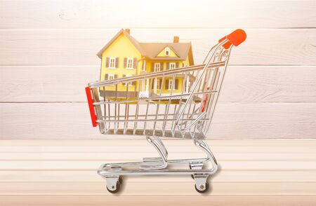 Classic house model  in shopping cart on backgrouund Imagens