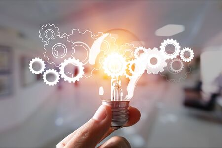Hand holding light bulb and cog inside. Idea and imagination. Creative and inspiration. Innovation gears icon with network connection on metal texture background. Innovative technology industrial. 版權商用圖片
