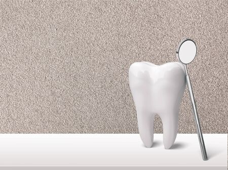 Big tooth and dentist mirror on table Stock Photo