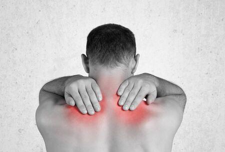 Rückansicht eines hemdlosen Mannes, der seinen schmerzenden Rücken berührt