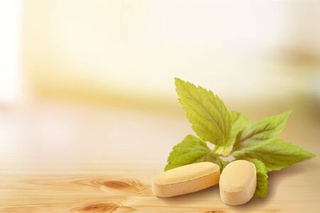 Organic pills with mint leaves on background