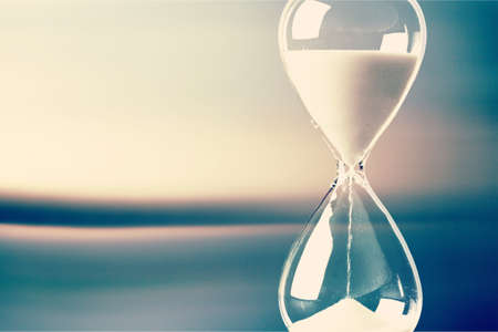 Modern Hourglass with blurry window-view background -- sand trickling through the bulbs of a crystal sand glass. every second counts. symbol of time. countdown. Banco de Imagens