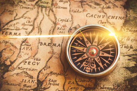 Antique bronze emblem compass, mini compass necklace pendant and binocular telescopes on ancient world map. (vintage style)