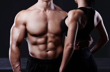 Junge sportliche Paare, die auf schwarzem Hintergrund aufwerfen. Schwarzweißfoto Standard-Bild