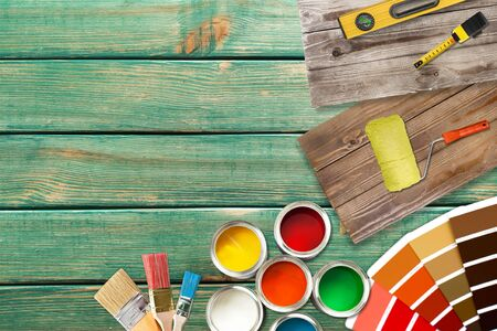Paint brushes and paint cans for  repair on wooden background
