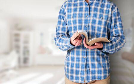 Hombre leyendo viejo libro pesado sobre fondo Foto de archivo