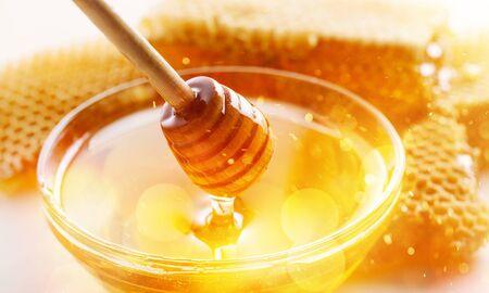 Honey with spoon in glass bowl on glossy background