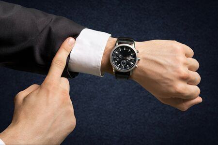 Businessman pointing at hand watch on white