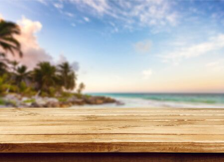 Wood table top over summer beach and clear blue sky background. Montage style to display the product.