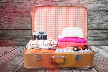 Retro luggage with colorful clothes on blurred background