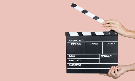 Hands holding clapper board on pink background