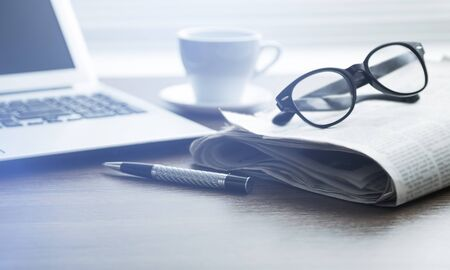 Newspapers with glasses and laptop. Online news.
