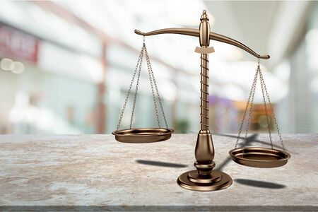 Gold-plated judge scales on wooden table