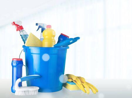 Botellas de plástico, esponjas de limpieza y guantes sobre fondo azul.