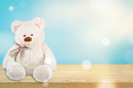 White Teddy bear sitting on a wooden table