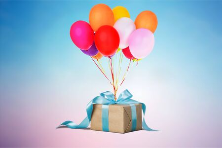 Gift box with colorful balloon on gradient background