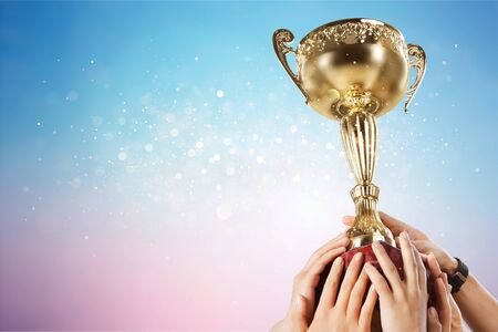 Hands holding golden trophy on light background Banco de Imagens