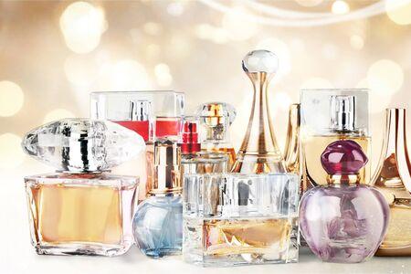 Aromatische Parfümflaschen auf weißem Holzschreibtisch am hölzernen Hintergrund Standard-Bild