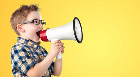 Small student speaks into the loudspeaker on a yellow background