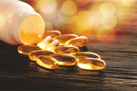 Fish oil capsules with omega 3 and vitamin D in a plastic bottle on a shiny texture with sun beams, healthy diet concept Stok Fotoğraf