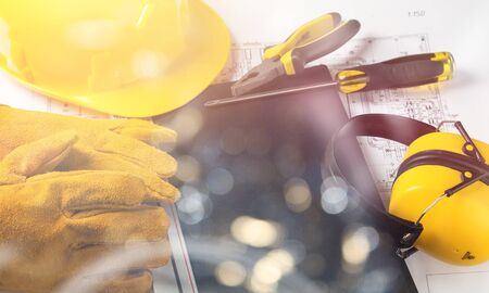 Yellow hard hat and blueprints in a construction concept